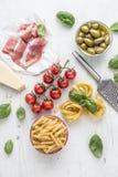 意大利或地中海食物烹调和成份在白色具体桌上 Tagliatelle pene面团橄榄橄榄油蕃茄 库存图片