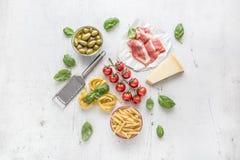意大利或地中海食物烹调和成份在白色具体桌上 Tagliatelle pene面团橄榄橄榄油蕃茄 免版税图库摄影
