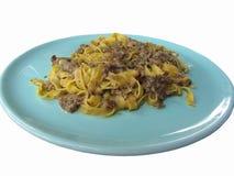 意大利新鲜的意大利细面条或tagliatelle面团与porcini在白色背景隔绝的一块蓝色板材采蘑菇 免版税库存照片