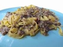 意大利新鲜的意大利细面条或tagliatelle面团与porcini在白色背景隔绝的一块蓝色板材采蘑菇 免版税库存图片
