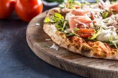 意大利比萨用熏火腿芝麻菜蕃茄和巴马干酪在w 库存照片