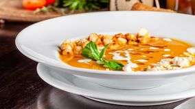 意大利烹调的概念 与橙色味道、鸡片断、面包油煎方型小面包片和奶油的南瓜奶油色汤 库存照片