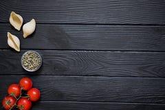 意大利烹调盘的成份在黑木桌后面 库存图片