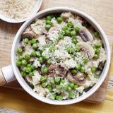 意大利煨饭有蘑菇豌豆和帕尔马干酪顶视图 库存图片