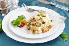 意大利煨饭用在一块白色板材的淡菜有蓬蒿的,在一块绿色布料的西红柿 概念吃健康 免版税库存图片