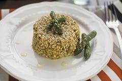 意大利煨饭用在陶瓷板材的芦笋在木桌上 免版税图库摄影