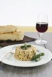 意大利煨饭用在陶瓷板材的芦笋在木桌 免版税库存图片