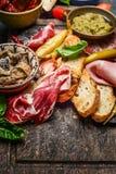 意大利熏制的火腿熏火腿用crostini面包和专业开胃小菜的在土气木背景 免版税图库摄影