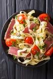 意大利细面条面团用在芝麻和菜的油煎的金枪鱼排 免版税库存照片