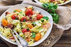 意大利细面条面团用被烘烤的蕃茄、烟肉和无盐干酪乳酪 免版税图库摄影