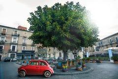 意大利老红色汽车在一个正方形的一棵树附近停放了在市卡塔尼亚在意大利 库存图片