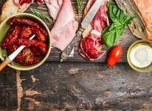 意大利肉板材用面包和开胃小菜在土气木背景,顶视图 免版税库存照片