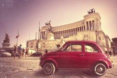意大利葡萄酒减速火箭的老红色汽车 在广场Venezia,罗马意大利的纪念碑 图库摄影