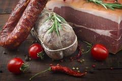 意大利蒜味咸腊肠、意大和辣香肠用西红柿和红辣椒和香料 库存照片