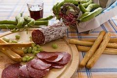 意大利蒜味咸腊肠蚕豆和面包条 免版税图库摄影