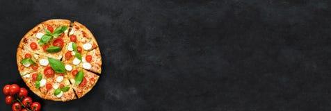 意大利薄饼用无盐干酪、蕃茄和蓬蒿在黑具体背景 图库摄影
