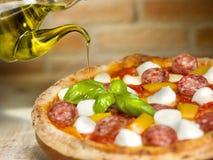 意大利薄饼用蕃茄、无盐干酪、胡椒蒜味咸腊肠和蓬蒿 免版税库存照片