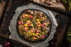 意大利薄饼用黑面团和海鲜在烘烤盘子从烤箱 图库摄影