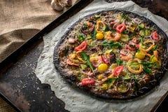 意大利薄饼用黑面团和海鲜在烘烤盘子从烤箱 免版税库存图片