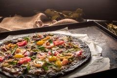 意大利薄饼用黑面团和海鲜在烘烤盘子从烤箱 库存图片
