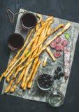 意大利语Grissini,猪肉香肠,橄榄,在黑暗的背景的红葡萄酒 免版税库存照片