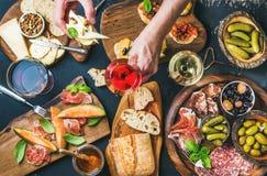 意大利酒快餐设置了,拿着玻璃的人的手上升了 免版税图库摄影