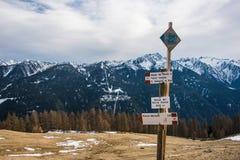 意大利阿尔卑斯、旅游标志-方向和雪靴,雪球拍 在背景的积雪覆盖的山 库存图片