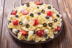 意大利面制色拉用无盐干酪、橄榄和蕃茄 库存照片