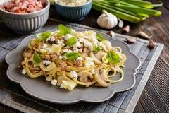 意大利面制色拉用油煎的烟肉、蘑菇、葱和乳酪 免版税库存照片