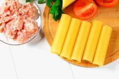 意大利面团烤碎肉卷子 充塞的烹调的成份围拢的充塞未加工的管,帕尔马干酪,蕃茄,剁碎了我 免版税图库摄影