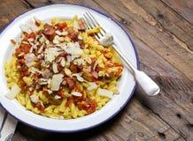 意大利面团用西红柿酱,熏制的pancetta,烤杏仁 库存照片