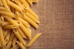 意大利面团的关闭和麻袋布背景 免版税库存照片