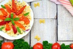 意大利面团farfalle蝴蝶弓领带用蕃茄在白色土气木桌的蓬蒿调味汁 库存图片
