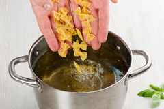 意大利面食准备 倒通心面的人的手入煮沸的o 免版税库存图片