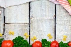 意大利食物烹调蕃茄、蓬蒿、面团、胡椒和蕃茄woden背景,顶视图,拷贝空间 库存图片