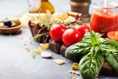 意大利食物背景用藤蕃茄,蓬蒿,意粉,在石桌拷贝空间的橄榄成份 免版税库存照片