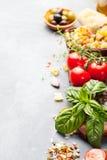 意大利食物背景用藤蕃茄,蓬蒿,意粉,橄榄,巴马干酪,橄榄油,大蒜 库存照片