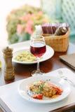 意大利食物-在白色板材的可口烤宽面条在桌上用红葡萄酒 免版税库存图片