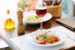 意大利食物-在白色板材的可口烤宽面条在桌上用红葡萄酒 图库摄影