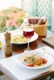 意大利食物-在白色板材的可口烤宽面条在桌上用红葡萄酒 免版税库存照片
