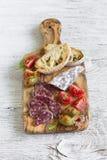 意大利香肠、面包ciabatta、橄榄和西红柿在橄榄色的委员会 免版税库存照片