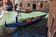意大利,威尼斯- 2012年7月:长平底船繁忙运输有巡航的游人的2012年7月16日的一条小运河在威尼斯。长平底船是a 库存照片