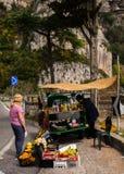 意大利,褶皱藻属,阿马飞- 4月11,2017的区域:一名年长妇女卖菜并且从一辆小汽车喝  免版税库存照片
