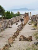 意大利,西尔苗内, Catullus Grotte di Catullo, Juli洞穴2013年:滑稽的专栏古老废墟的游人  免版税库存照片