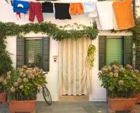 意大利, Burano : 有花和洗衣店停止的房子 免版税库存照片