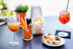意大利aperitives/开胃酒:两杯在桌上的鸡尾酒和开胃菜盛肉盘 免版税图库摄影