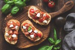 意大利bruschetta开胃小菜用蕃茄、无盐干酪乳酪和蓬蒿在木委员会 免版税库存图片