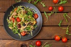 意大利bucatini用虾、芝麻菜和西红柿 木背景 特写镜头 顶视图 免版税图库摄影