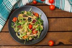 意大利bucatini用虾、芝麻菜和西红柿 木背景 特写镜头 顶视图 免版税库存照片