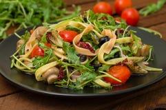 意大利bucatini用虾、芝麻菜和西红柿 木背景 特写镜头 顶视图 库存图片